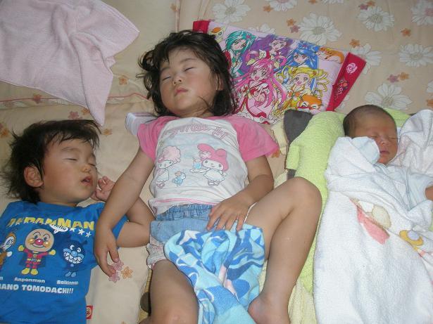 子供が三人熟睡している写真